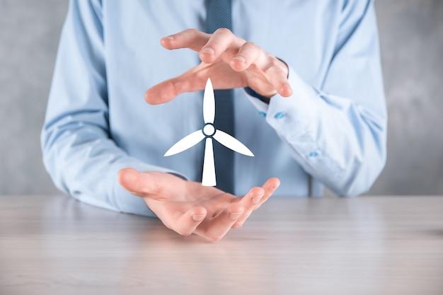 Homme d'affaires détenant une icône d'un moulin à vent qui produit de l'énergie environnementale