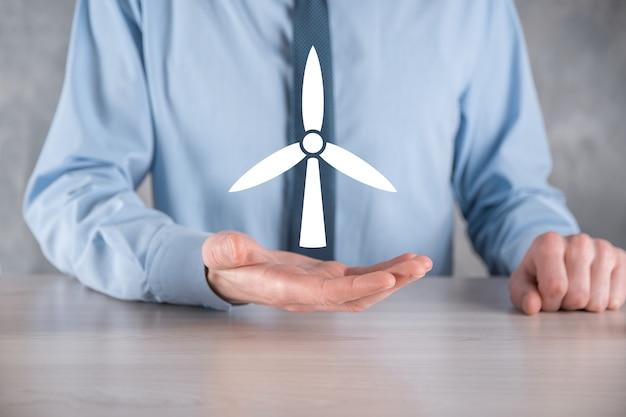 Homme d'affaires détenant une icône d'un moulin à vent qui produit de l'énergie environnementale.