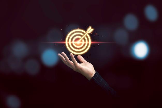 Homme d'affaires détenant un jeu de fléchettes cible dorée virtuelle pour le concept d'objectif commercial de mise au point et de réalisation.