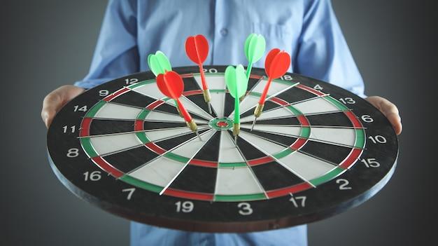 Homme d'affaires détenant un jeu de fléchettes avec des flèches. cible, entreprise, succès