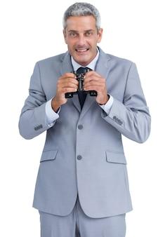 Homme d'affaires détenant des jumelles dans les deux mains