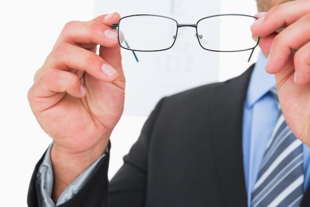 Homme d'affaires détenant des lunettes