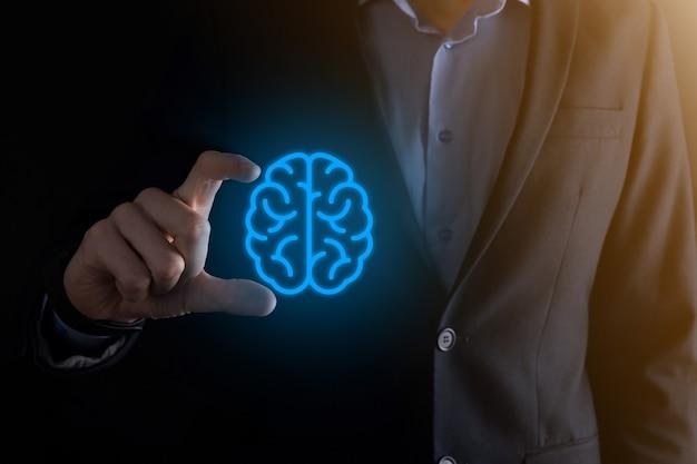 Homme d'affaires détenant des outils abstraits de cerveau et d'icône, un appareil, une communication de connexion réseau client sur une technologie future de développement virtuel et innovant, la science, l'innovation et le concept commercial.