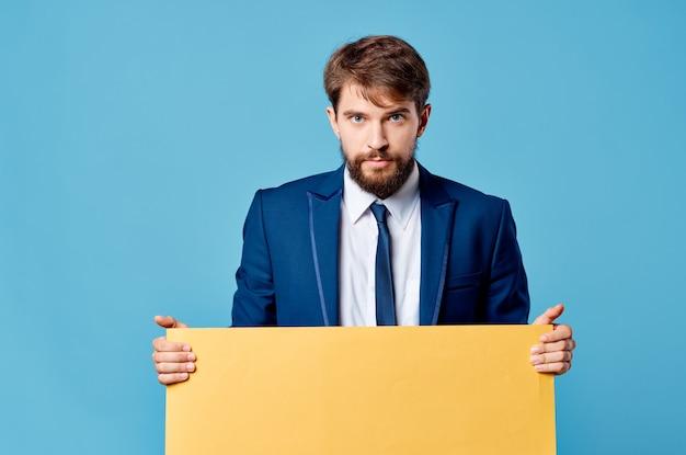 Homme d'affaires détenant un panneau publicitaire promotionnel sur fond bleu.