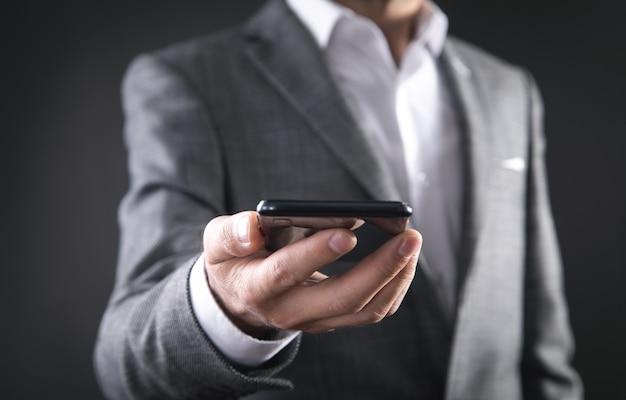 Homme d'affaires détenant un smartphone au bureau.