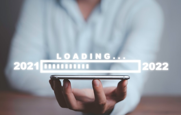 Homme d'affaires détenant un smartphone avec barre de progression de chargement pour le réveillon du nouvel an et changement d'année 2021 à 2022.