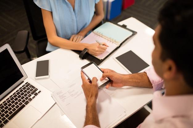 Homme d'affaires détenant un téléphone mobile alors qu'il était assis avec un collègue au bureau