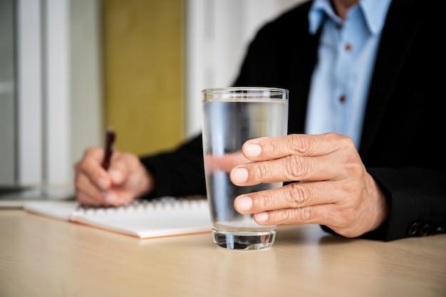 Homme d'affaires détenant un verre d'eau froide sur la table en bois dans son bureau.