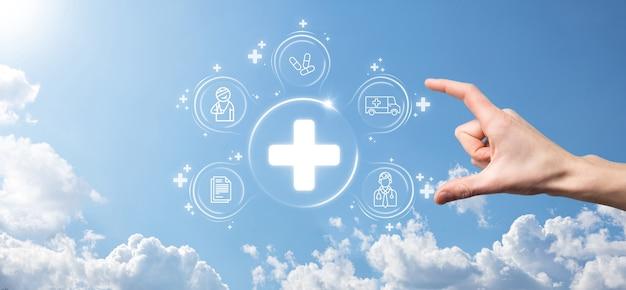 Homme d'affaires détiennent des icônes de connexion réseau virtuel et médical. la pandémie de covid-19 sensibilise les gens et répartit l'attention sur leurs soins de santé.médecin, document, médecine, ambulance, icône du patient.