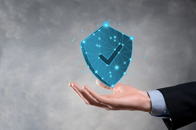 Un homme d'affaires détient un bouclier de polygone low poly avec une icône de coche. concept de système d'accès sécurisé. garantie financière d'entreprise pour l'investissement. concept antivirus. sécurité de la technologie. réseau de protection, données sécurisées.