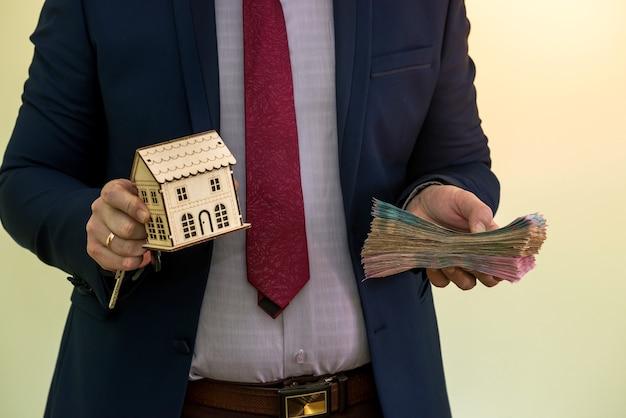 Un homme d'affaires détient les clés de l'appartement avec l'argent de quelqu'un après avoir vendu ou loué une maison. conclure un accord réussi