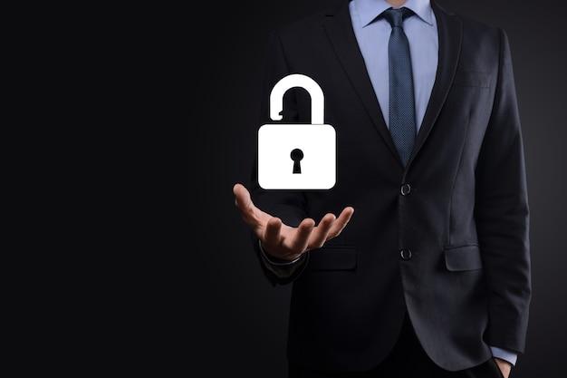L'homme d'affaires détient une icône de cadenas ouvert sur sa paume. déverrouillant un verrou virtuel. concept commercial et métaphore technologique pour la cyberattaque, la criminalité informatique, la sécurité de l'information et le cryptage des données.
