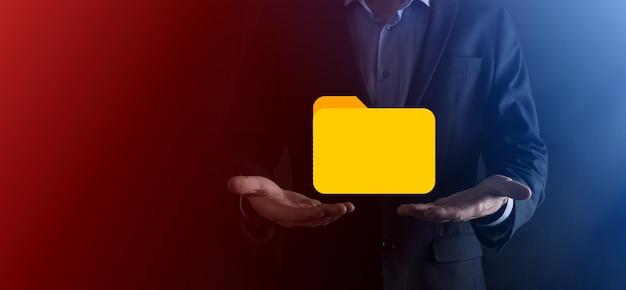 L'homme d'affaires détient l'icône du dossier. le système de gestion des documents ou la configuration dms par un consultant en informatique avec un ordinateur moderne recherchent des informations de gestion et des fichiers d'entreprise. traitement commercial.
