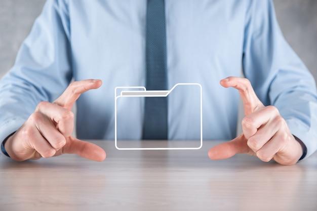 L'homme d'affaires détient l'icône du dossier. le système de gestion des documents ou la configuration dms par un consultant en informatique avec un ordinateur moderne recherchent des informations de gestion et des fichiers d'entreprise.