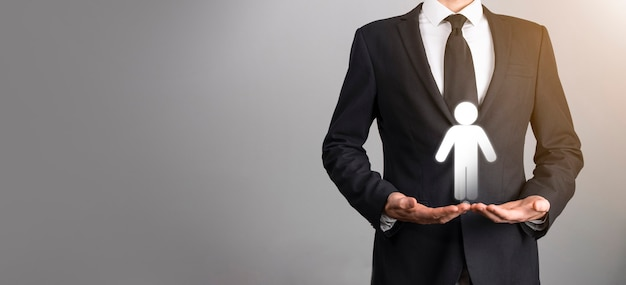 L'homme d'affaires détient l'icône de la personne de l'homme sur fond de ton sombre. hr human, people icontechnology process system business avec recrutement, embauche, création d'équipe. notion de structure organisationnelle.