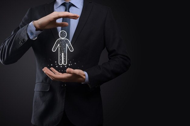 L'homme d'affaires détient l'icône de la personne de l'homme sur fond de ton sombre. hr human, people icontechnology process system business avec recrutement, embauche, création d'équipe notion de structure organisationnelle.
