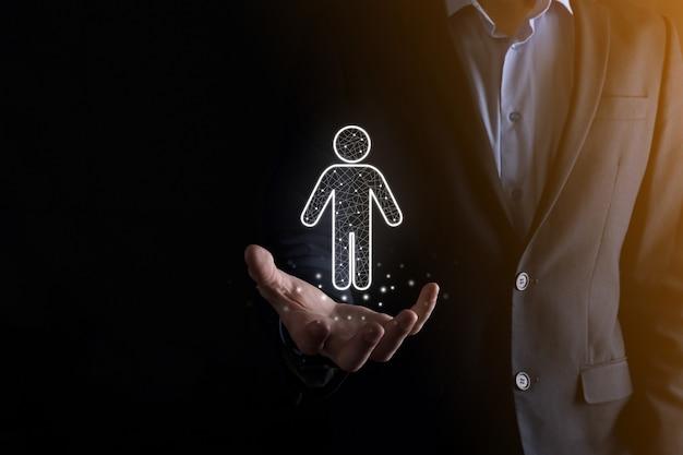 Homme d'affaires détient l'icône de personne homme sur fond de ton sombre.