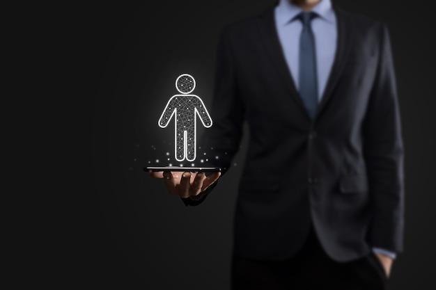 Homme d'affaires détient l'icône de personne homme sur le mur de ton sombre. hr humain, icône de personnes concept de structure organisationnelle.