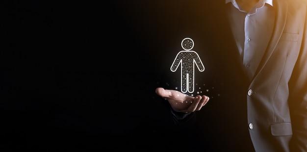 Homme d & # 39; affaires détient l & # 39; icône de la personne homme sur le mur de ton sombre. hr humain, icône de personnes