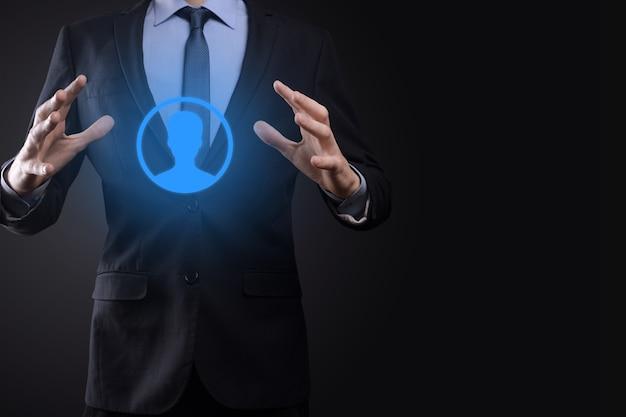 Homme d'affaires détient l'icône de personne homme sur le mur de ton sombre.