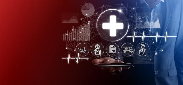 L'homme d'affaires détient des icônes de connexion réseau virtuel et médical. la pandémie de covid-19 développe la sensibilisation des gens et attire l'attention sur leurs soins de santé. médecin, document, médecine, ambulance, icône du patient.