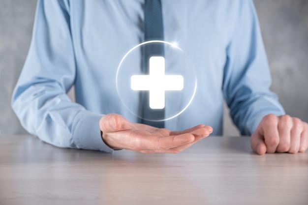 L'homme d'affaires détient des icônes de connexion réseau virtuel et médical. la pandémie de covid-19 sensibilise les gens et attire l'attention sur leurs soins de santé.