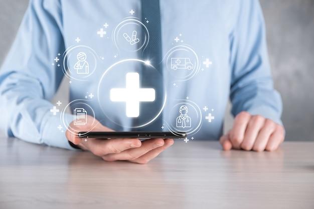 L'homme d'affaires détient des icônes de connexion réseau virtuelles et médicales. la pandémie de covid-19 développe les gens