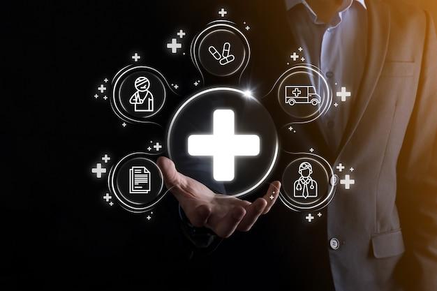 L'homme d'affaires détient des icônes de connexion réseau virtuelles et médicales. la pandémie de covid-19 développe la sensibilisation des gens et attire l'attention sur leurs soins de santé. médecin, document, médecine, ambulance, icône du patient.