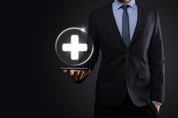 L'homme d'affaires détient des icônes de connexion réseau virtuelles et médicales. la pandémie de covid-19 sensibilise les gens et attire l'attention sur leurs soins de santé.