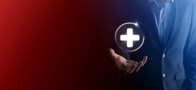 L'homme d'affaires détient des icônes de connexion réseau virtuelles et médicales. la pandémie de covid-19 sensibilise les gens et attire l'attention sur leurs soins de santé