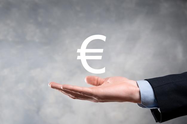 Homme d'affaires détient des icônes de pièces d'argent eur ou euro sur fond de ton sombre