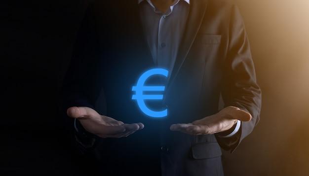 Homme d'affaires détient des icônes de pièces d'argent eur ou euro sur le mur de ton sombre. concept d'argent croissant pour les investissements et les finances des entreprises.