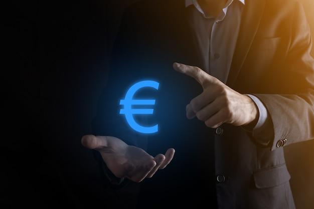 Homme d'affaires détient des icônes de pièces d'argent eur ou euro sur un mur de ton sombre. concept de plus en plus d'argent pour les investissements et les finances des entreprises.