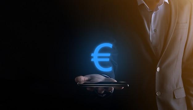 Homme d'affaires détient des icônes de pièces d'argent (eur ou euro) sur ton sombre.concept d'argent croissant pour l'investissement et la finance des entreprises.