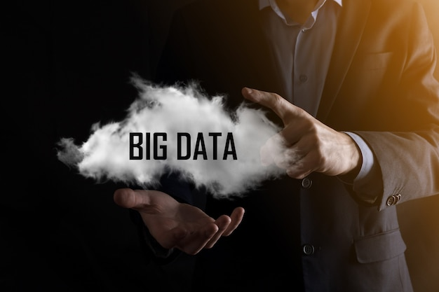 L'homme d'affaires détient l'inscription big data. cadenas, cerveau, homme, planète, graphique, loupe, engrenages, nuage, grille, document, lettre, icône de téléphone.