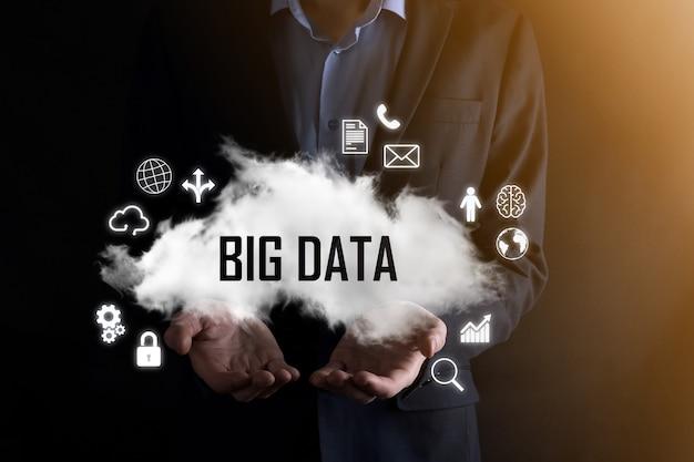 L'homme d'affaires détient le mot d'inscription big data. cadenas, cerveau, homme, planète, graphique, loupe, engrenages, nuage, grille, document, lettre, icône de téléphone.