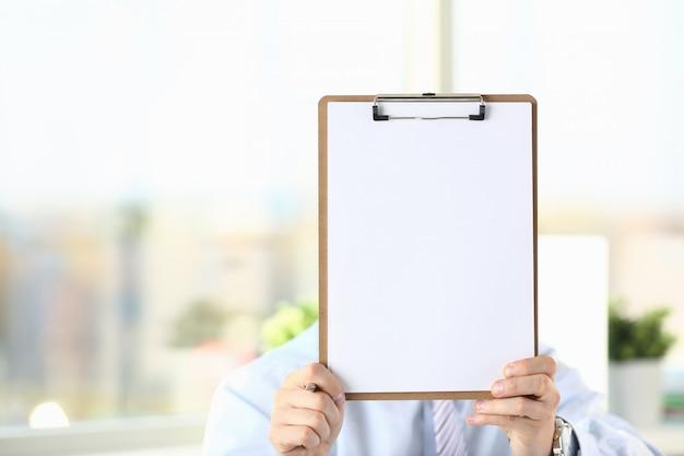 Homme d'affaires détient le presse-papiers avec du papier