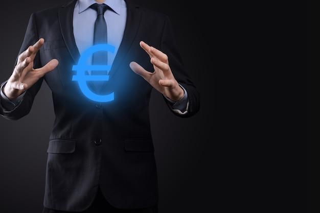 Homme d'affaires détient des symboles de pièces d'argent eur ou euro sur un mur de ton sombre. concept d'argent croissant pour les investissements et les finances des entreprises.
