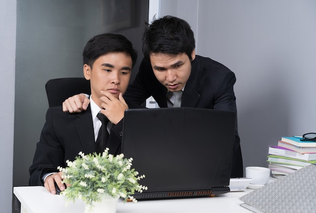 Homme d'affaires deux utilisant un ordinateur portable et de discuter du projet