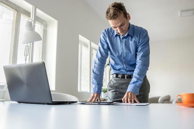 Homme d'affaires dévoué travaillant sur de la paperasse à une table de bureau avec un ordinateur portable ouvert devant lui dans une vue en contre-plongée sur la surface du bureau avec espace de copie.