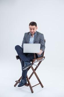 Homme d'affaires directeur d'enseignant assis sur une chaise étudiant des documents. il regarde l'écran de l'ordinateur portable. nouveau projet d'entreprise.