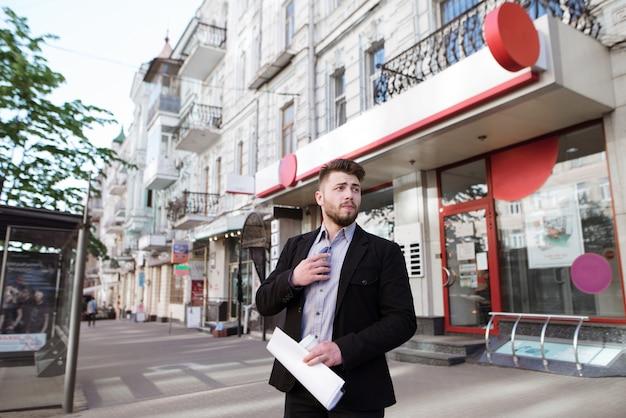 Homme affaires, documents, sien, mains, debout, rue, entrée, bureau