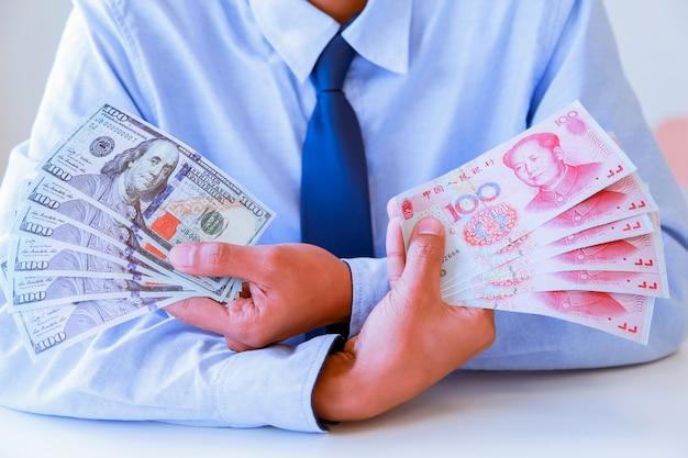 Homme d'affaires avec dollar en espèces, yuan