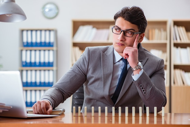 Homme d'affaires avec des dominos au bureau