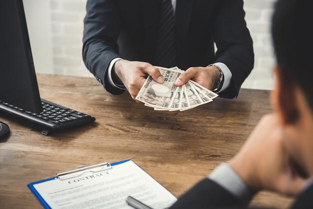 Homme d'affaires donnant de l'argent, billet de banque en yen japonais, à son partenaire tout en concluant un contrat