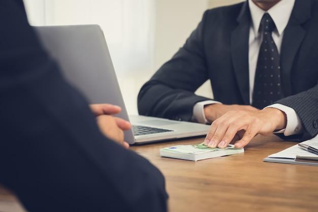 Homme d'affaires donnant de l'argent, des billets en euros, à son partenaire sur un bureau