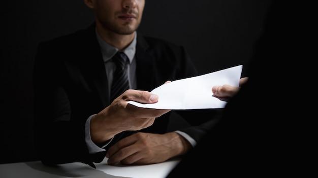 Homme d'affaires donnant de l'argent dans l'enveloppe pour partenaire