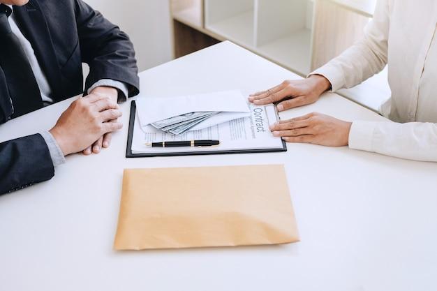 Homme d'affaires donnant de l'argent dans l'enveloppe tout en faisant affaire à un accord cont immobilier