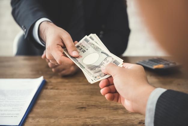 Homme d'affaires donnant de l'argent, devise du yen japonais, à son partenaire