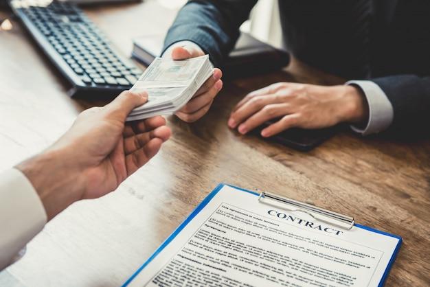 Homme d'affaires donnant de l'argent, en dollars américains, à son partenaire lors de la conclusion du contrat